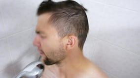 Il ritratto dell'uomo barbuto divertente canta e ballo nel bagno Lavaggi del tipo nella doccia stock footage