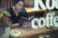 Il ritratto dell'uomo bianco bello dei pantaloni a vita bassa ha letto un libro in caffè vicino alla finestra Fotografia Stock