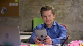 Il ritratto dell'uomo d'affari biondo di mezza età funziona in ufficio facendo uso della compressa con soddisfazione e letizia video d archivio