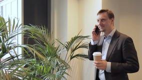 Il ritratto dell'uomo d'affari che discute i suoi piani per il fine settimana sul telefono con i suoi amici stock footage