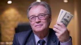 Il ritratto dell'uomo d'affari senior in costume convenzionale mostra il pacchetto di soldi nella macchina fotografica che è feli archivi video