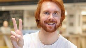 Il ritratto dell'uomo della barba della testarossa che gesturing la vittoria firma dentro il caffè immagine stock libera da diritti