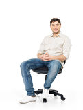 Il ritratto dell'uomo felice sorridente si siede sulla presidenza dell'ufficio Immagine Stock Libera da Diritti