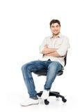 Il ritratto dell'uomo felice sorridente si siede sulla sedia dell'ufficio Fotografia Stock