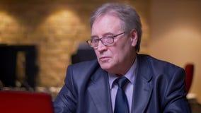 Il ritratto dell'uomo senior in costume convenzionale che ha un video rivolge al computer portatile che è allegro e positivo in u video d archivio