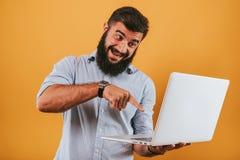 Il ritratto dell'uomo sorridente bello isolato sul fondo giallo dello studio che posa alla macchina fotografica e che fa i fronti Fotografia Stock Libera da Diritti