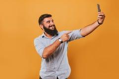 Il ritratto dell'uomo sorridente bello isolato sul fondo giallo dello studio che posa alla macchina fotografica e che fa i fronti Fotografie Stock Libere da Diritti