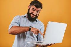 Il ritratto dell'uomo sorridente bello isolato sul fondo giallo dello studio che posa alla macchina fotografica e che fa i fronti Fotografia Stock
