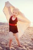 Il ritratto della bambina sorridente felice adorabile sveglia del bambino con l'asciugamano sulla spiaggia che fa le pose affront Fotografie Stock Libere da Diritti