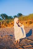 Il ritratto della bambina sorridente felice adorabile sveglia del bambino con l'asciugamano sulle dune insabbia divertiresi della Fotografia Stock Libera da Diritti