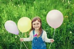 Il ritratto della bambina sveglia con il bello giocattolo della tenuta di sorriso balloons a disposizione sul prato del fiore, in Fotografie Stock Libere da Diritti
