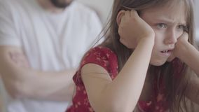 Il ritratto della bambina triste che si siede sulla priorità alta che tiene la sua testa in mani si chiude su Il padre con le arm video d archivio