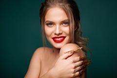 Il ritratto della donna abbastanza sexy con le labbra rosse, rosso e chiodi di bellezza dell'oro, inchioda la decorazione, gioiel immagini stock libere da diritti