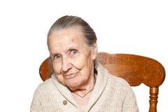Il ritratto della donna anziana dai capelli grigi, nonna, sedentesi sulla sedia marrone d'annata, isola il fondo bianco Concetto  fotografia stock