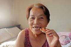 Il ritratto della donna asiatica anziana sta sorridendo vede il dente rotto immagini stock