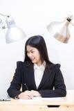 Il ritratto della donna asiatica di affari con il computer portatile scrive sull'i documen Fotografia Stock
