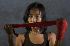 Il ritratto della donna cinese asiatica del combattente sportivo ed adatto che per mezzo del polso avvolge lo spostamento prima c immagine stock