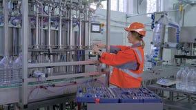 Il ritratto della donna dell'ingegnere alla fabbrica, di forte femmina felice in abiti da lavoro e del casco ripara professionale video d archivio