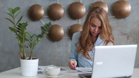 Il ritratto della donna di affari con il computer portatile scrive su un documento al suo ufficio stock footage