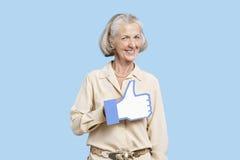 Il ritratto della donna senior in falsificazione casuale della tenuta gradisce il bottone contro fondo blu Immagini Stock Libere da Diritti