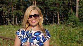 Il ritratto della donna sorridente con la camomilla fiorisce la condizione nel parco all'aperto archivi video