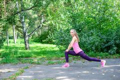 Il ritratto della donna sportiva che fa l'allungamento si esercita in parco prima della formazione Atleta femminile che prepara p Fotografie Stock