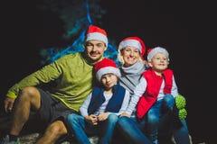 Il ritratto della famiglia amichevole in Santa ricopre l'esame della macchina fotografica sull'uguagliare di Natale Immagini Stock Libere da Diritti