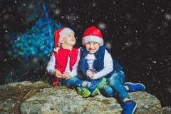 Il ritratto della famiglia amichevole in Santa ricopre l'esame della macchina fotografica sull'uguagliare di Natale Fotografie Stock Libere da Diritti