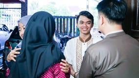 Il ritratto della famiglia a casa accoglie favorevolmente e stringe le mani mentre abbraccia con gli amici musulmani fotografia stock