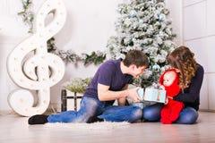 Il ritratto della famiglia di Natale nel salone domestico di festa, il contenitore di regalo attuale, Camera che decora dall'albe Fotografia Stock
