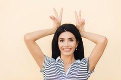 Il ritratto della femmina castana felice fa il gesto del corno, si diverte e i foolishes con gli amici, essendo nel buon umore, i immagini stock