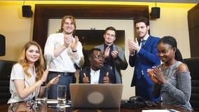 Il ritratto della gente di affari felice del gruppo guarda alla macchina fotografica ed applaude il loro successo di affari stock footage