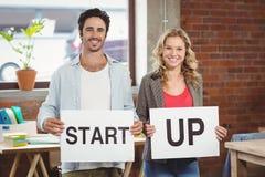 Il ritratto della gente di affari sorridente che mostra la carta con inizia sul testo in ufficio Immagine Stock
