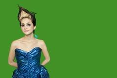 Il ritratto della giovane donna appuntita dei capelli con le mani dietro appoggia sopra fondo verde fotografia stock libera da diritti