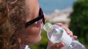 Il ritratto della giovane donna beve l'acqua dalla bottiglia video d archivio