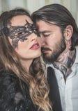 Il ritratto della giovane donna con una maschera del pizzo ha preso in giro dall'uomo elegante a Immagine Stock Libera da Diritti
