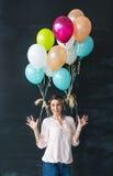 Il ritratto della giovane donna sveglia che sta in uno studio, giocante con il colorfull balloons contro lo sfondo della parete n Fotografia Stock Libera da Diritti