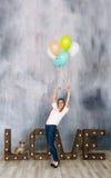 Il ritratto della giovane donna sveglia che sta in uno studio, sorridente ampiamente e giocante con il colorfull balloons Immagini Stock
