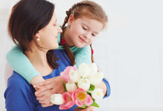 Il ritratto della madre felice e la figlia con la molla fioriscono il mazzo immagini stock