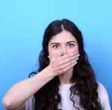 Il ritratto della ragazza che arrossisce con consegna la bocca contro la parte posteriore del blu Immagine Stock
