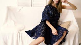 Il ritratto della ragazza con le belle gambe lunghe posa sullo strato all'interno, tiro di foto alla moda in studio video d archivio