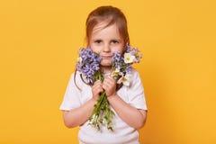 Il ritratto della ragazza del bambino con il mazzo dei fiori del giardino isolati sopra il fondo giallo dello studio, aspetta per fotografia stock