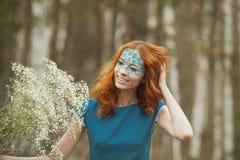 Il ritratto della ragazza del redhair in vestito blu con il respiro del bambino fiorisce in primavera la foresta Immagine Stock