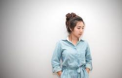 Il ritratto della ragazza graziosa dell'Asia che posa le mani in tasche si veste Immagine Stock Libera da Diritti