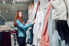 Il ritratto della ragazza rossa dei capelli nella donna blu del bomber shopaholic fa un acquisto nel supermercato Etichetta stagi fotografia stock