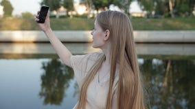 Il ritratto della ragazza sexy dei pantaloni a vita bassa, riscalda i colori tonificati fabbricazione del selfie, divertendosi archivi video