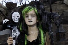 Il ritratto della ragazza si è agghindato come strega mentre i suoi amici si sono agghindati in costume di scheletro Immagine Stock