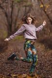 Il ritratto della ragazza sportiva in camicia bianca esegue il riscaldamento prima di pareggiare nella foresta di autunno Fotografie Stock