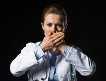 Il ritratto della rappresentazione della donna di medico non parla gesto diabolico Immagini Stock