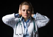 Il ritratto della rappresentazione della donna di medico non sente gesto diabolico Immagine Stock